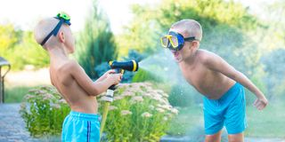 Two brothers play on a summer hot day in the garden. Children are splashing with a garden hose. Children are splashing with a garden hose.Two brothers play on stock images
