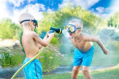 Two brothers play on a summer hot day in the garden. Children are splashing with a garden hose. Children are splashing with a garden hose.Two brothers play on a stock photography