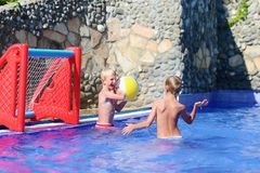 Two brothers playing with ball in swimming pool. Two happy teenage boys, sportive twin brothers, having fun together playing waterpolo with colorful inflatable Stock Photo