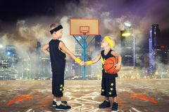Two brothers playing basketball in the street. stock image