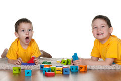 Two brothers playing blocks on the floor Stock Photos