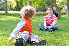 Two brothers playing in the grass Stock Images