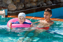 Two brothers playing in the pool Royalty Free Stock Images