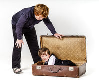 Two brothers playing with retro suitcase Royalty Free Stock Photo