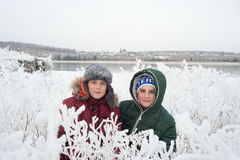 Two brothers playing in the snow with a view of Royalty Free Stock Photos