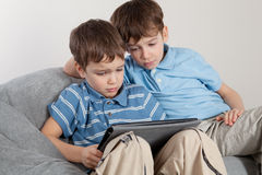 Two brothers playing on tablet Royalty Free Stock Image