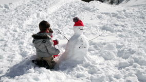 Two brothers playing together with snow stock video footage