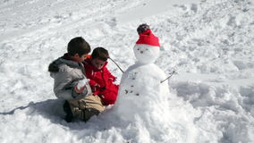 Two brothers playing together with snow stock footage