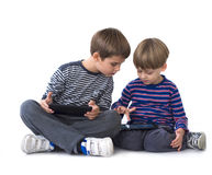 Two brothers playing video games on tablets Royalty Free Stock Image