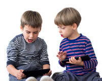 Two brothers playing video games on tablets Stock Images