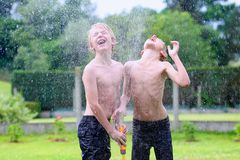 Two brothers playing with water hose in the garden. Happy laughing children, two young school boys, enjoying hot sunny summer vacation day playing outdoors in royalty free stock photography
