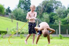 Two brothers playing with water hose in the garden. Happy laughing children, two young school boys, enjoying hot sunny summer vacation day playing outdoors in royalty free stock images