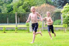 Two brothers playing with water hose in the garden. Happy laughing children, two young school boys, enjoying hot sunny summer vacation day playing outdoors in stock photos
