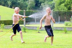 Two brothers playing with water hose in the garden. Happy laughing children, two young school boys, enjoying hot sunny summer vacation day playing outdoors in royalty free stock image