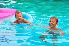 Two brothers  in the pool. Two brothers are swimming in the pool Stock Photo