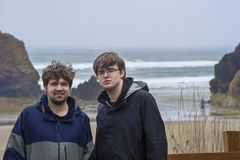 Two Brothers pose for camera. Two brothers pose, in the rain, for camera before heading out on  Arcadia beach seen in the background on the Oregon Coast Stock Images