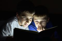 Two brothers reading a book. Hiding in the dark and using a torch light. Selective focus Stock Images