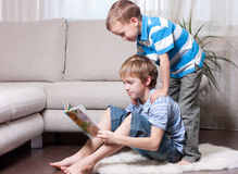 Two brothers are reading books. Stock Image