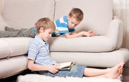Two brothers are reading books. Stock Photo