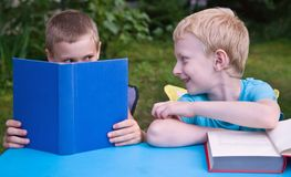 Two brothers reading books and discussing. 8-year schoolboy and 6-year preschooler reading books and discussing outdoors Royalty Free Stock Photo