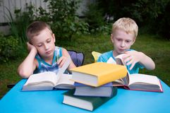 Two brothers reading books outdoors Stock Image