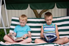 Two brothers reading books outdoors Stock Photo