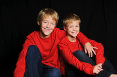Two brothers in red shirt on black background. Stock Photo