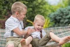The two brothers are resting and having fun .Children ride in a hammock. stock photos