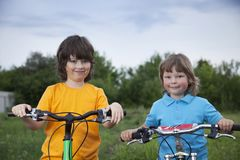 Two brothers ride bikes. Outdoors Stock Photo