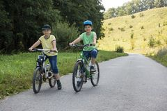 Two brothers ride bikes summer outdoors. Two brothers ride bikes summer outdoors royalty free stock image