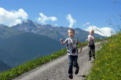 Two brothers running on mountain path Royalty Free Stock Photos
