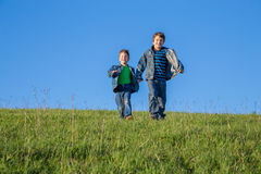 Two brothers running together on green meadow against blue sky. Two happy brothers running together on green grass against blue sky Stock Image
