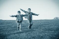 Two brothers running together on meadow, sepia toned Royalty Free Stock Images