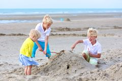 Two brothers and sister playing on the beach. Group of three smiling children, preschooler girl and teenage boys playing together on the beach building sand Stock Images