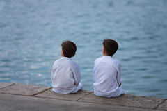 Two brothers sit on beach and look at sea Stock Photos
