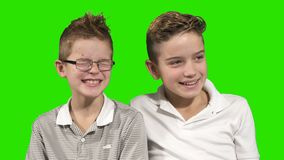 Two brothers laughing at green background. Two brothers sits at green background and looks outside the camera. Adorable boys looks sometimes on each other and stock footage
