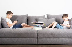 Two brothers sits in the opposite side of the sofa and looks on tablet computers. Two brothers sits in the opposite side of the sofa and looks on the tablet royalty free stock photos