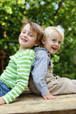 Two brothers sitting back to back laughing Royalty Free Stock Images