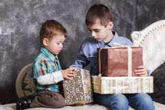Two brothers sitting on the bed opening New Year`s gifts in boxes. Christmas royalty free stock images