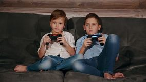 Two brothers sitting on the couch and very emotional playing video games with wireless joystick. stock video