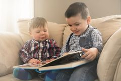 Two brothers sitting embracing on the couch read a book royalty free stock photos