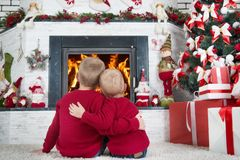 Merry Christmas and Happy Holidays!Two brothers sitting on the floor in the living room and look at the fire in the fireplace.In a royalty free stock photo