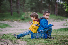 Two brothers sitting in the forest eating Royalty Free Stock Photos