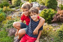 Two brothers outdoors. Two brothers are sitting and hugging outdoors Stock Photography