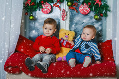 Two brothers sitting on new year decorated window Royalty Free Stock Photo