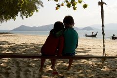 Two Brothers sitting on a swing in Thailand stock photo