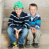 Two brothers. Smiling two brothers sitting on the stairs outdoors Stock Photo