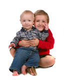 Two Brothers Smiling and Sitting Together on White Royalty Free Stock Photo