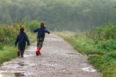 Two brothers splashing in puddles.  Royalty Free Stock Images