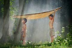 Two brothers standing by with a bamboo boat on a head in rural T Stock Photo